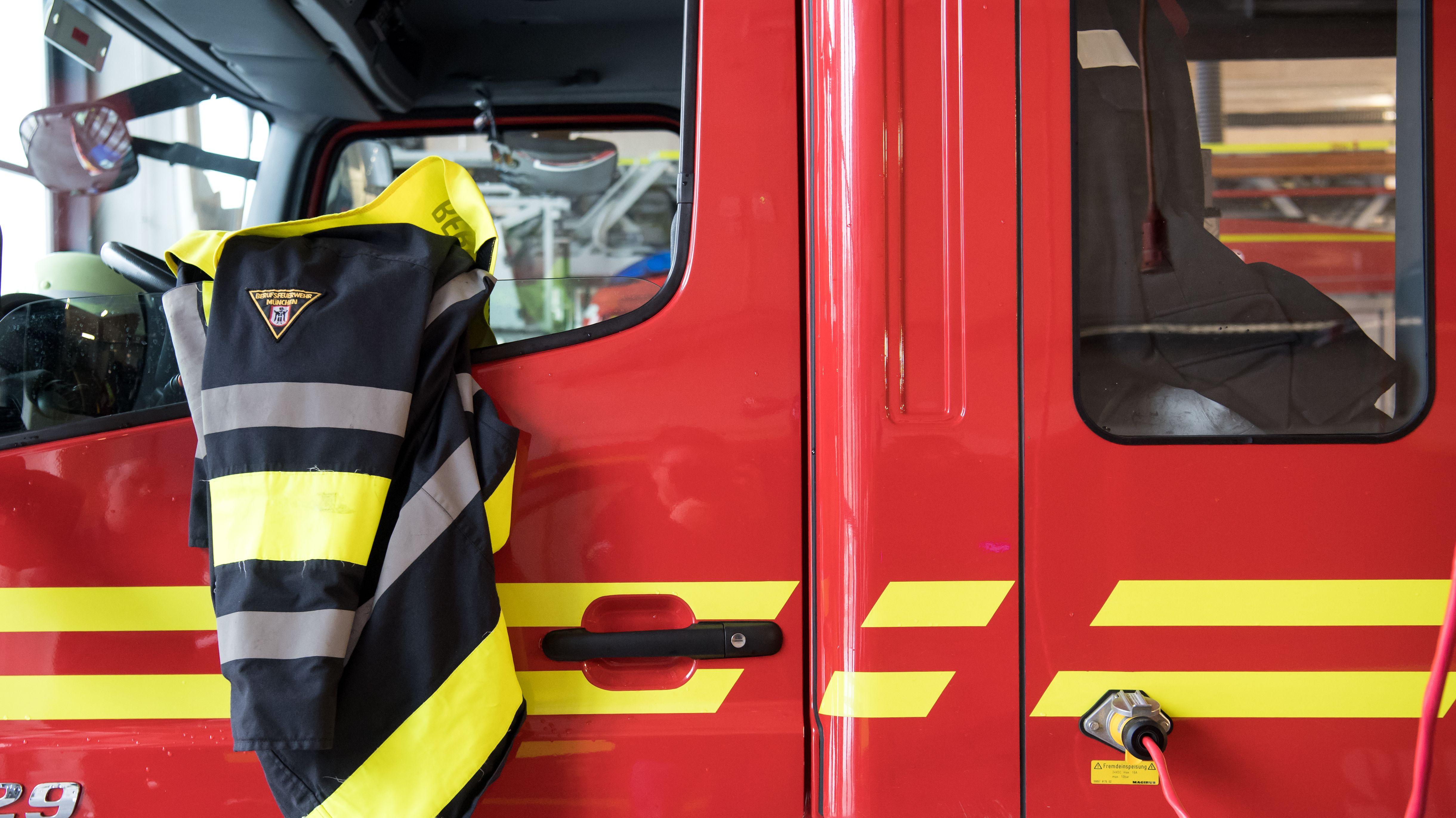 Eine Feuerwehrjacke der Berufsfeuerwehr München hängt an einem Feuerwehrfahrzeug