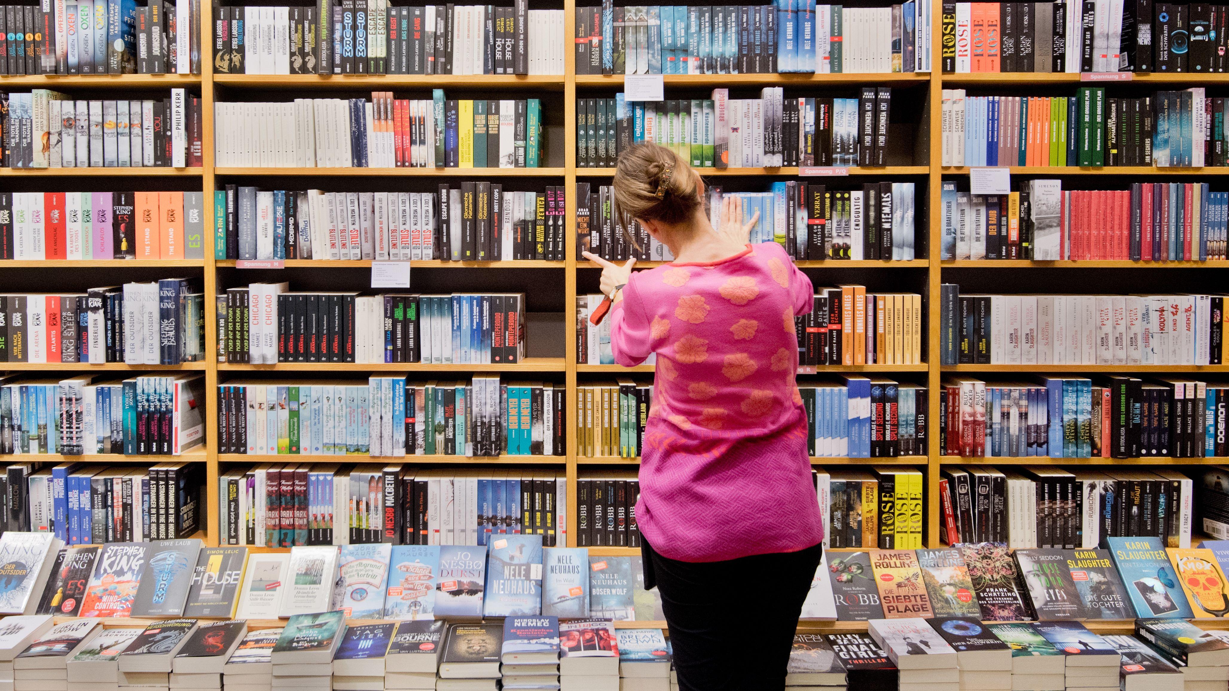 Eine Buchhändlerin sortiert die Auslage in einer Filiale