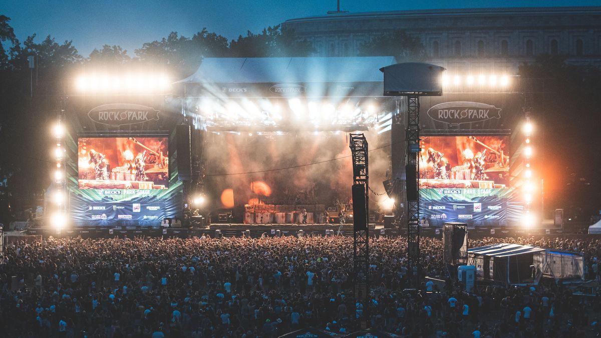 Menschenmenge vor einer hell erleuchteten Open-Air-Bühne.
