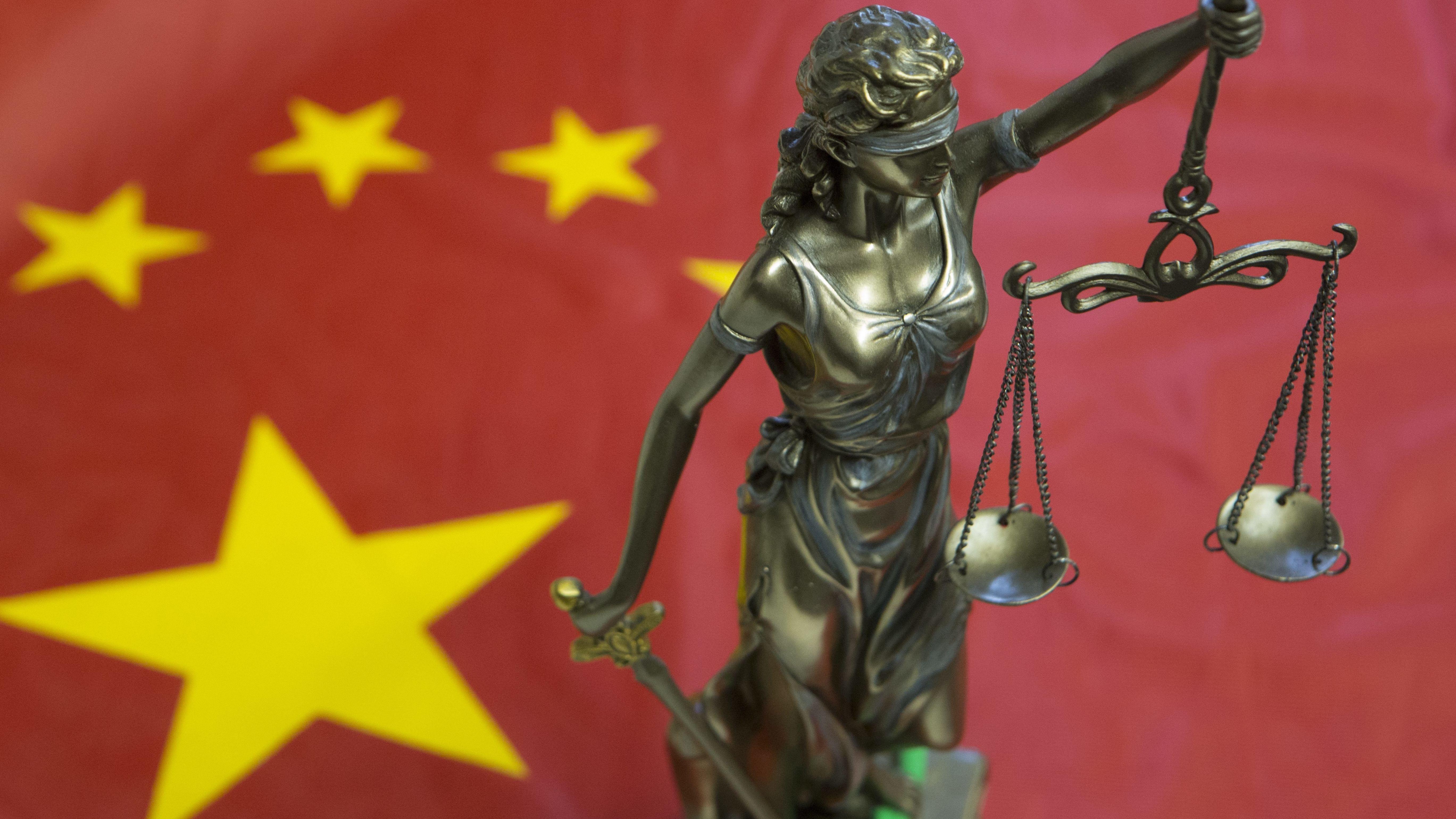 Eine Statue der Justitia steht auf einer China-Fahne.