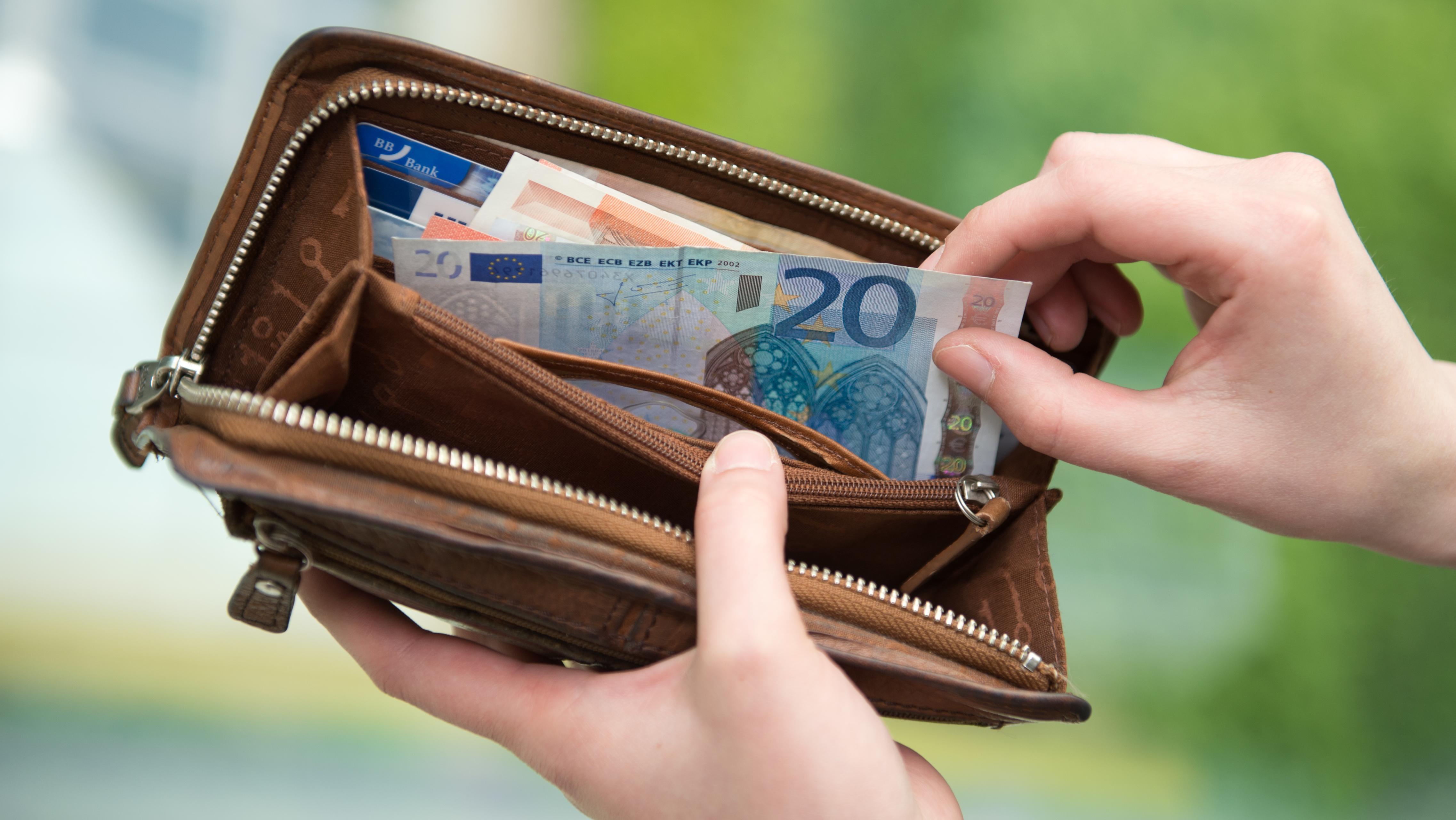 Eine Frau nimmt Geldscheine aus einem Portemonnaie