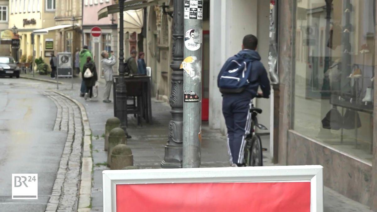 Ein Fahrradfahrer ist mit seinem Rad auf dem Gehsteig unterwegs.