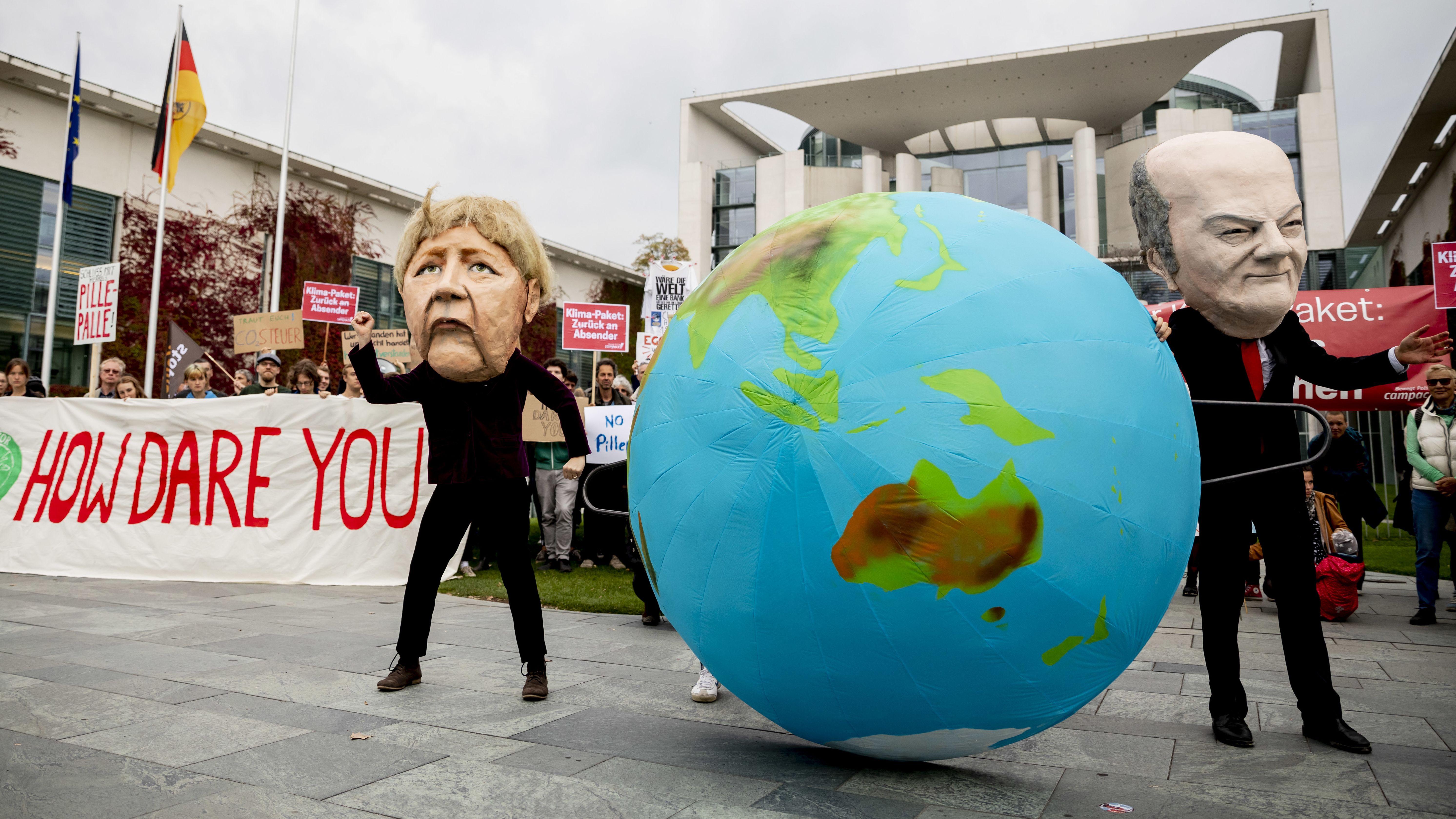 """Zwei Darsteller tragen bei einer Kundgebung von Fridays for Future und der Nichtregierungsorganisation Campact gegen die Klimapolitik der Bundesregierung vor dem Bundeskanzleramt und einem Banner mit der Aufschrift """"How dare you?"""" (Wie könnt ihr es wagen?) Masken, die Bundeskanzlerin Angela Merkel (CDU, M) und Olaf Scholz (SPD, r), Bundesfinanzminister, zeigen."""