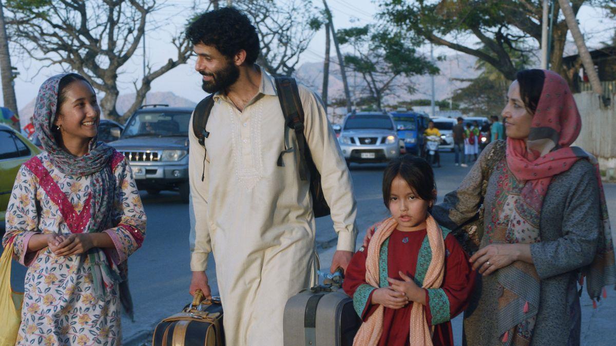 """Eine vierköpfige Familie geht, mit Koffern in den Händen eine Straße entlang. Szene aus der Serie """"Stateless""""."""
