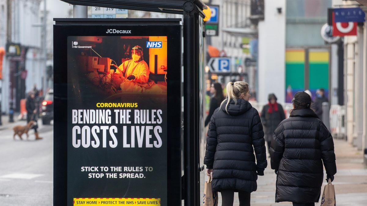 Frauen gehen an einer Plakatwand mit Corona-Warnung vorbei