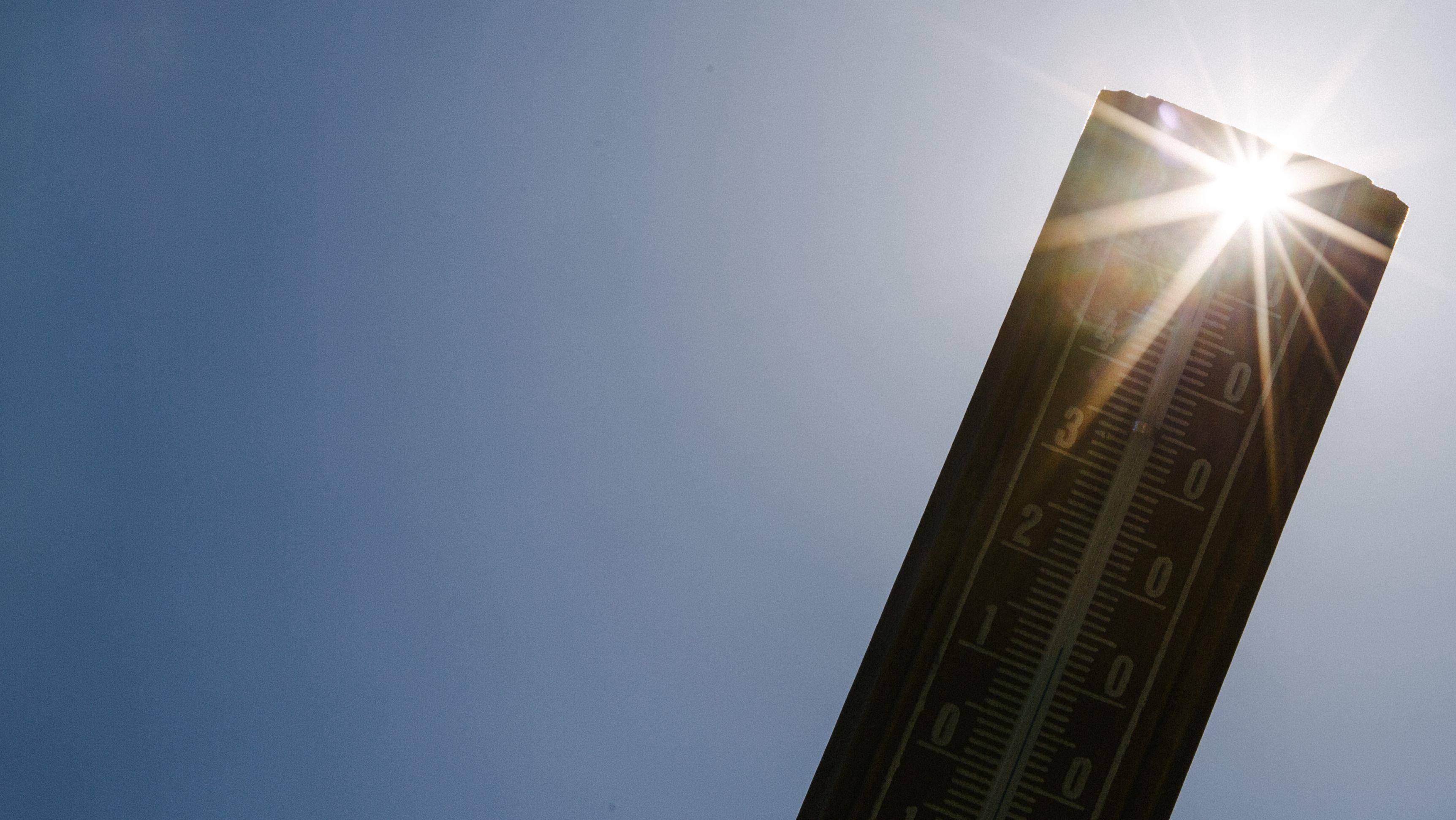 Ein Thermometer mit der Sonne im Hintergrund