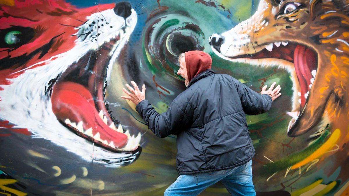Mann steht vor einer Graffiti-Wand