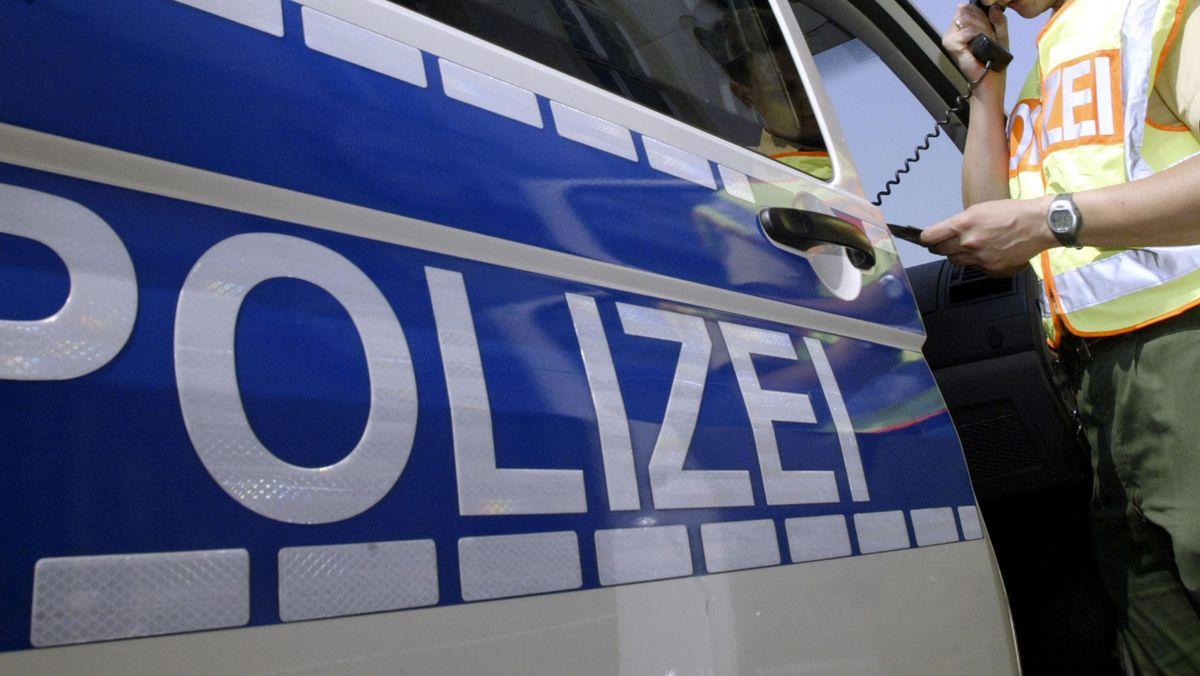 Ein Bundespolizist überprüft die Personalien eines Autofahrers an einer Bundestraße