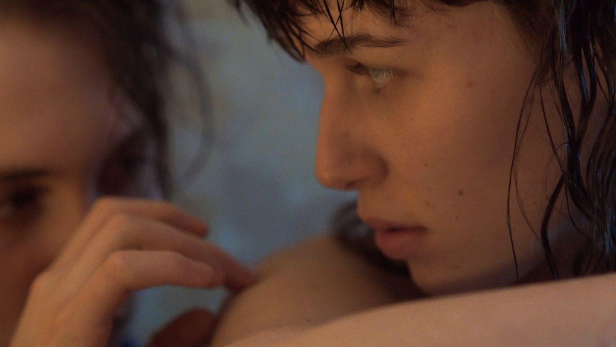 Filmszene mit zwei Jugendlichen in Nahaufnahme, die sich vorsichtig berühren.
