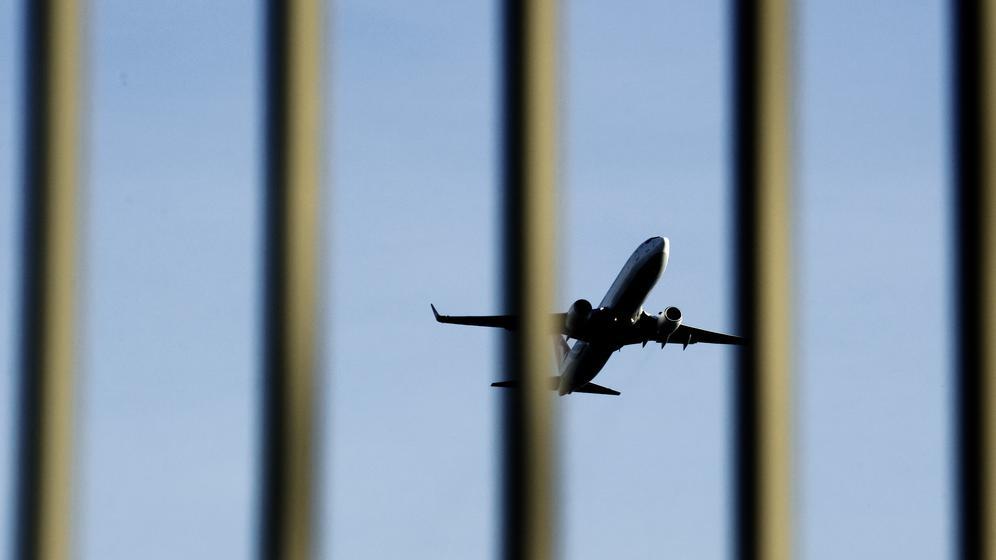Blick auf Flugzeug durch Gitterstäbe | Bild:picture alliance