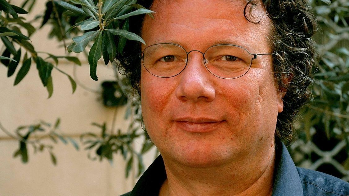 Ein Farbporträt des Schriftstellers Ingo Schulze, vor grüner Pflanze