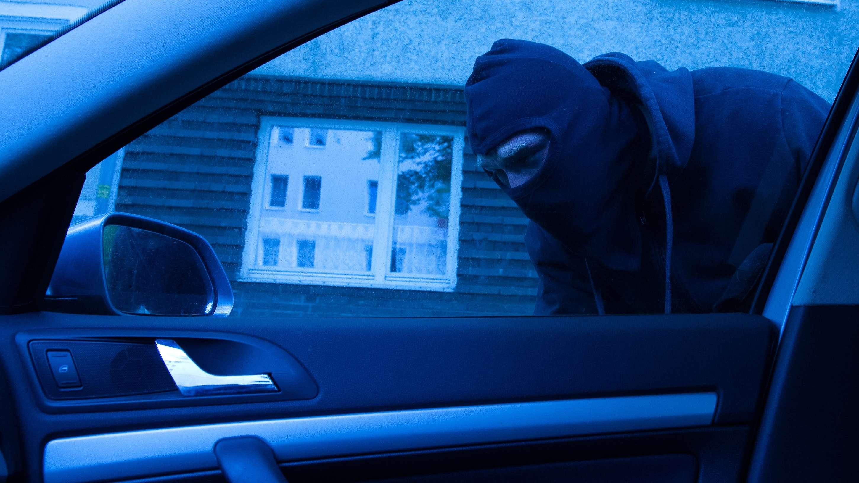 Ein Maskierter schleicht sich an ein Auto ran