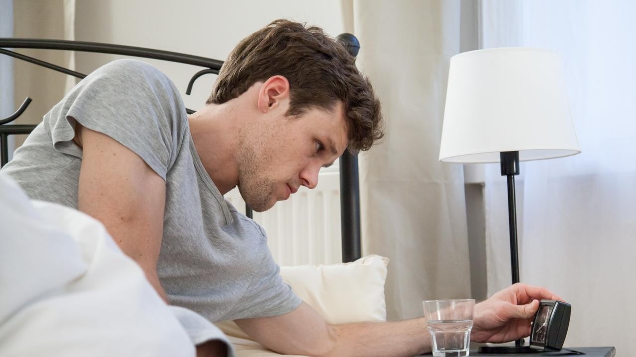 Ein Mann liegt wach in seinem Bett und schaut auf den Wecker auf seinem Nachttisch. Die Hälfte der Erwerbstätigen leidet unter Schlafstörungen.