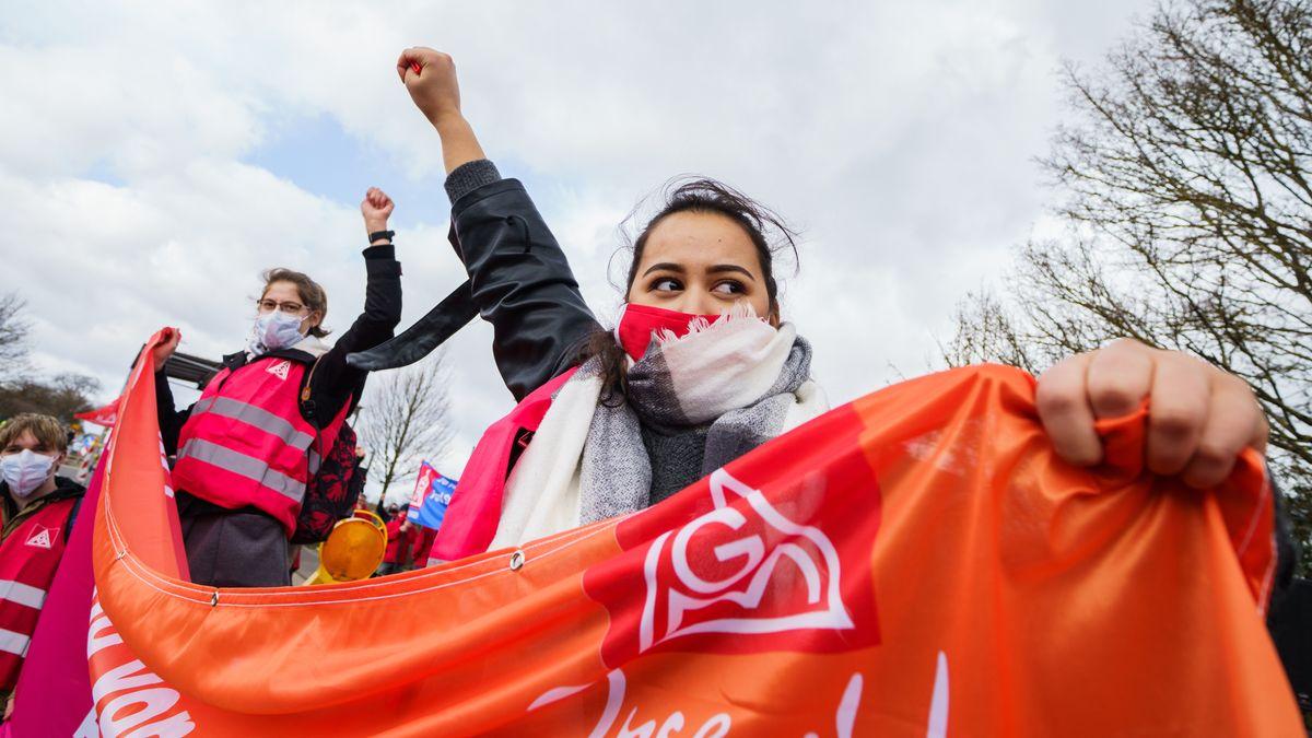Kundgebungsteilnehmerinnen demonstrieren mit erhobener Faust