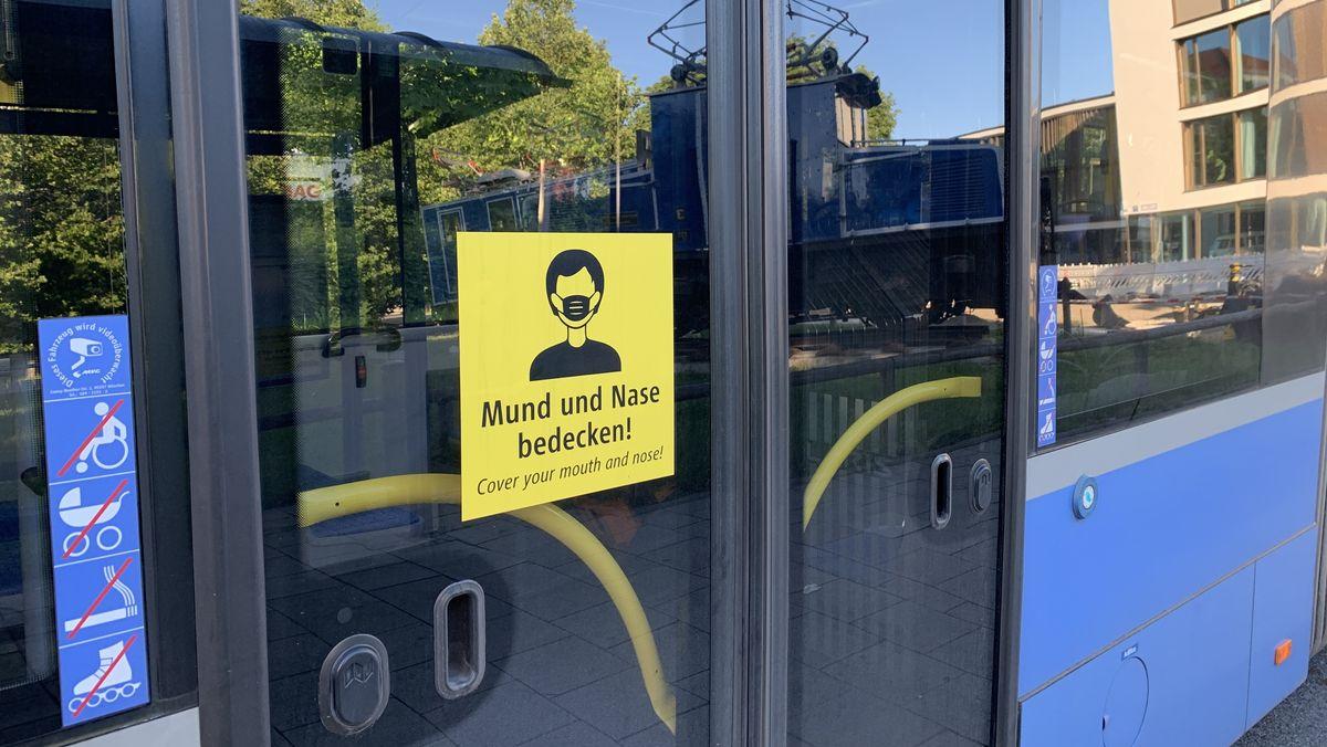 """Ein Aufkleber mit der Aufforderung """"Mund und Nase bedecken"""" an der Tür eines Münchner Busses."""