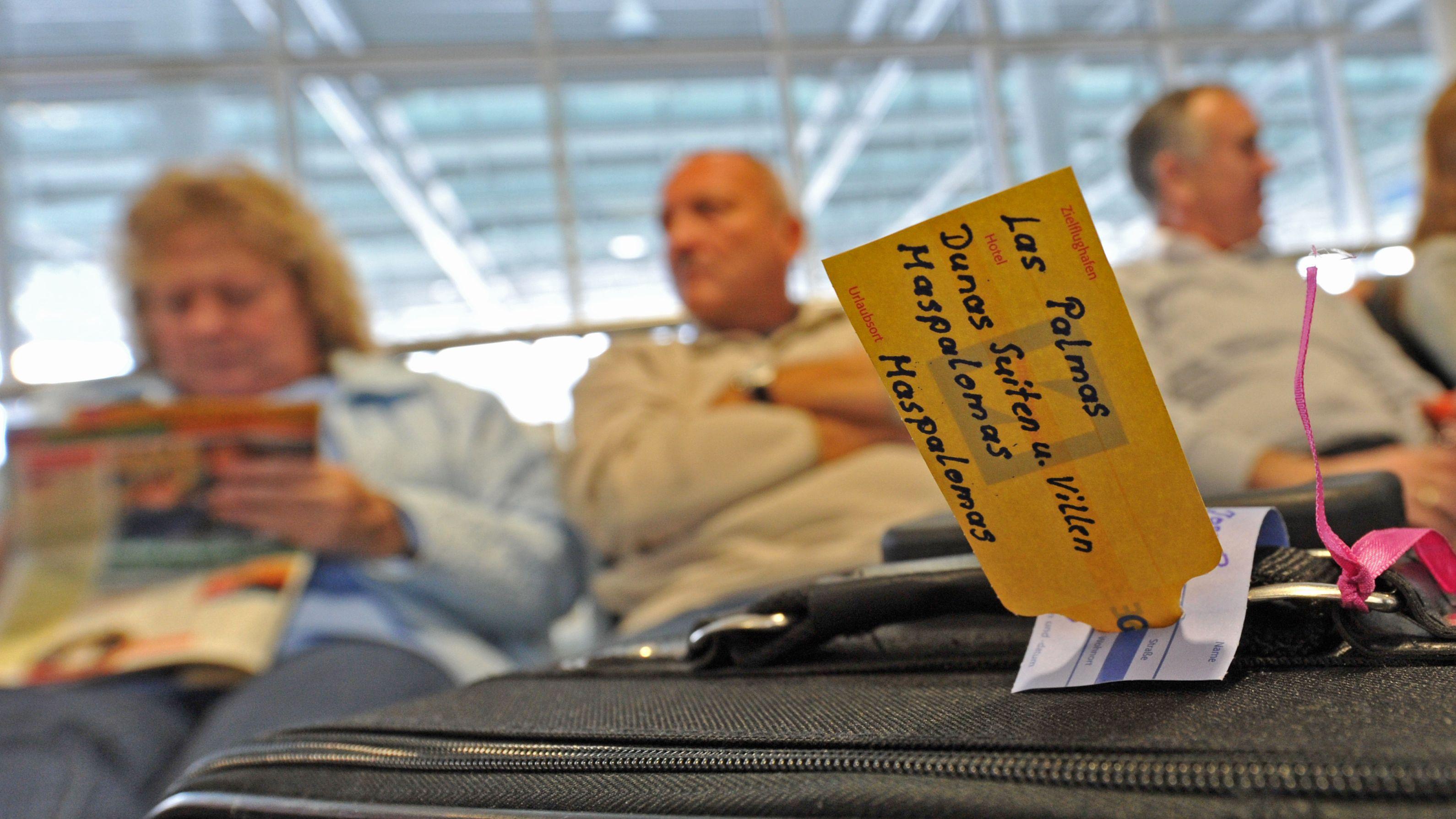 Passagiere warten am Flughafen München auf ihren Abflug