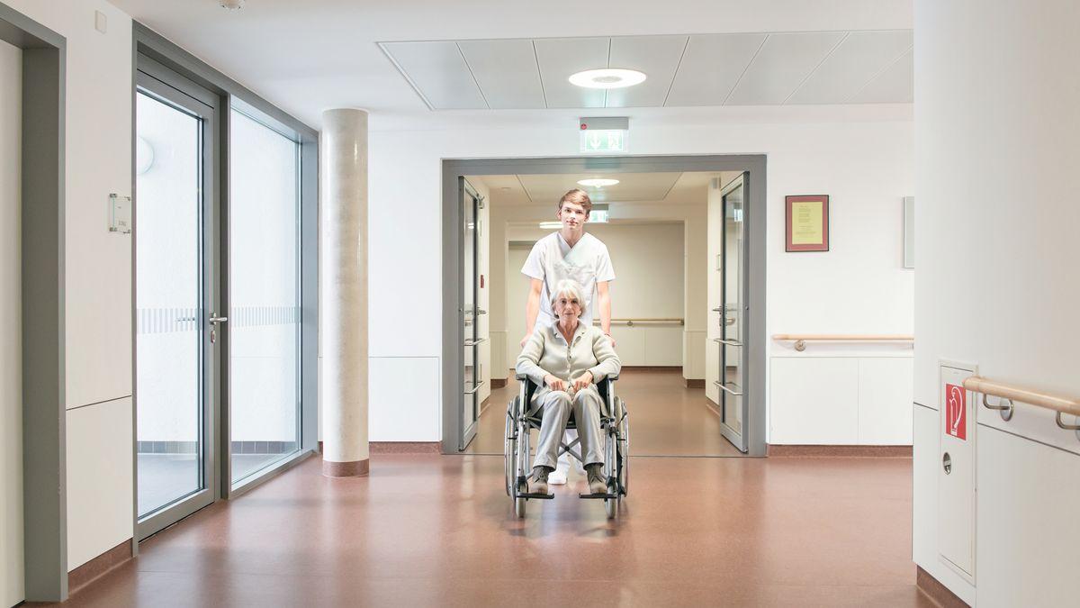 Krankenpfleger schiebt ältere Patientin im Rollstuhl durch einen Krankenhausflur (Symbolbild)