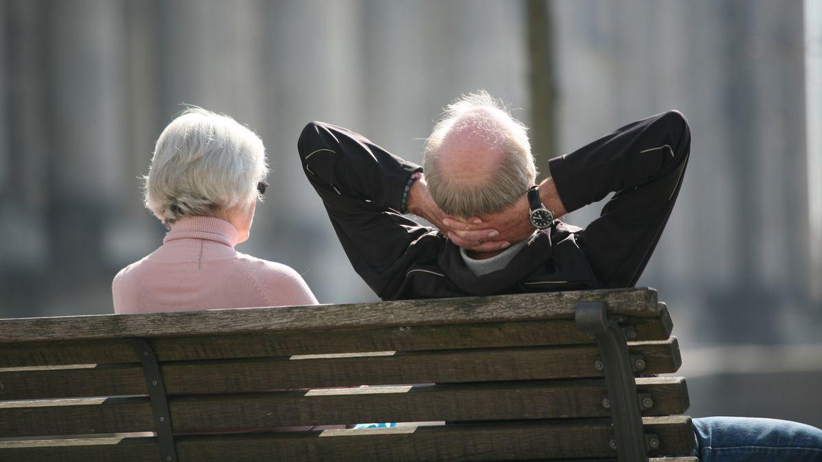 Ein Rentnerpaar sitzt auf einer Bank und sonnt sich