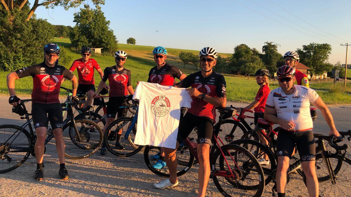 """Eine Gruppe von acht Rennradfahrern, der Mann in der Mitte zeigt das Siegertrikot des Vereins """"Radeln und Helfen"""". Das bekommt jeder, der 8.848 Höhenmeter radelt, innerhalb von 24 Stunden."""
