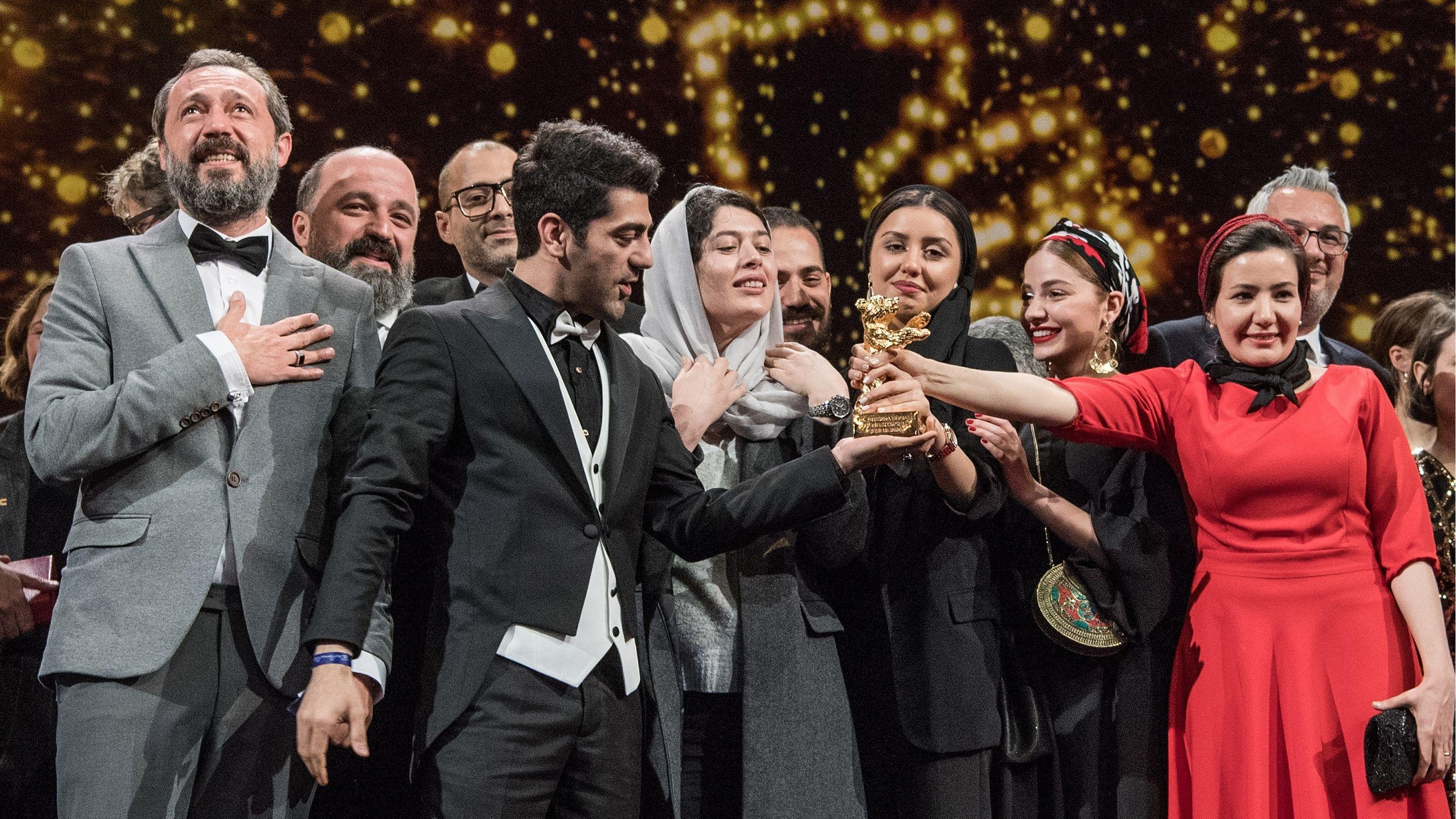 """Auch der Bühne stehen Menschen, die sich sehr freuen. Sie halten den goldenen Bären hoch: Das Team des iranischen Films """"There is no evil"""" am Samstag Abend bei der Verleihung des Goldenen Bären der Berlinale"""