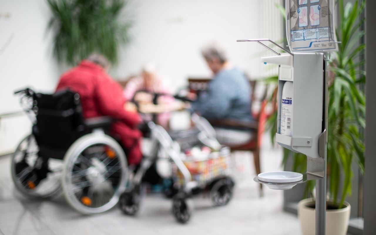 symbolbild: Ein Desinfektionsmittelspender hängt in einem Altenheim während im Hintergrund Seniorinnen spielen.