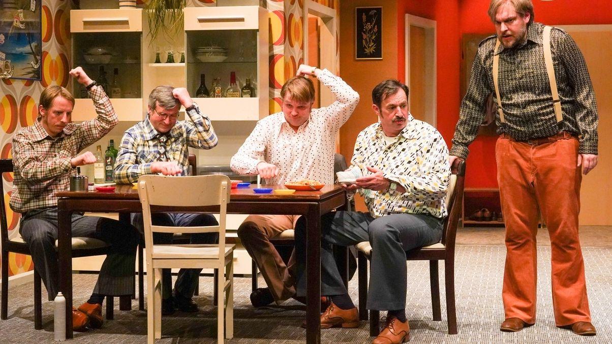 Fünf Schauspieler stehen und sitzen auf der Bühne.