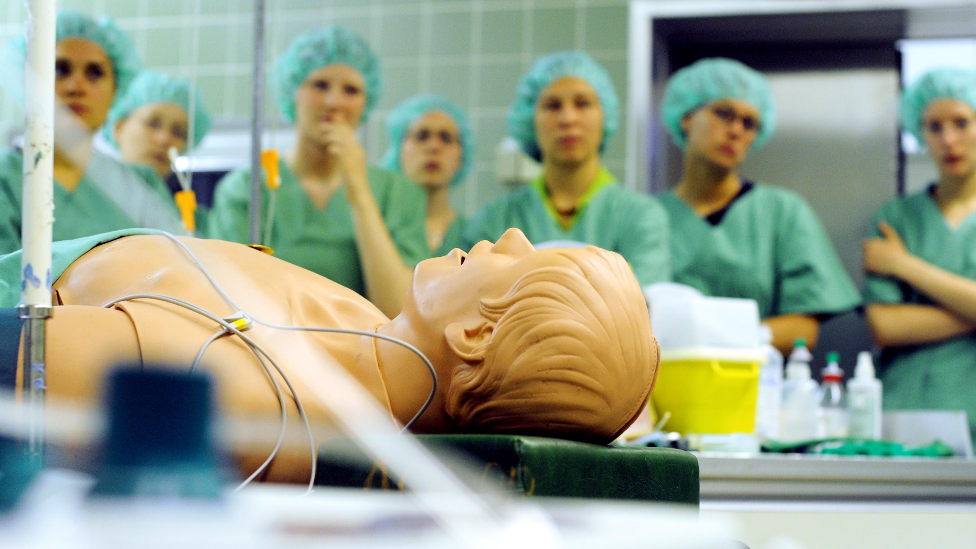 Mehrere Medizinstudenten stehen in einem Operationssaal in grünen Kitteln um eine Puppe herum.