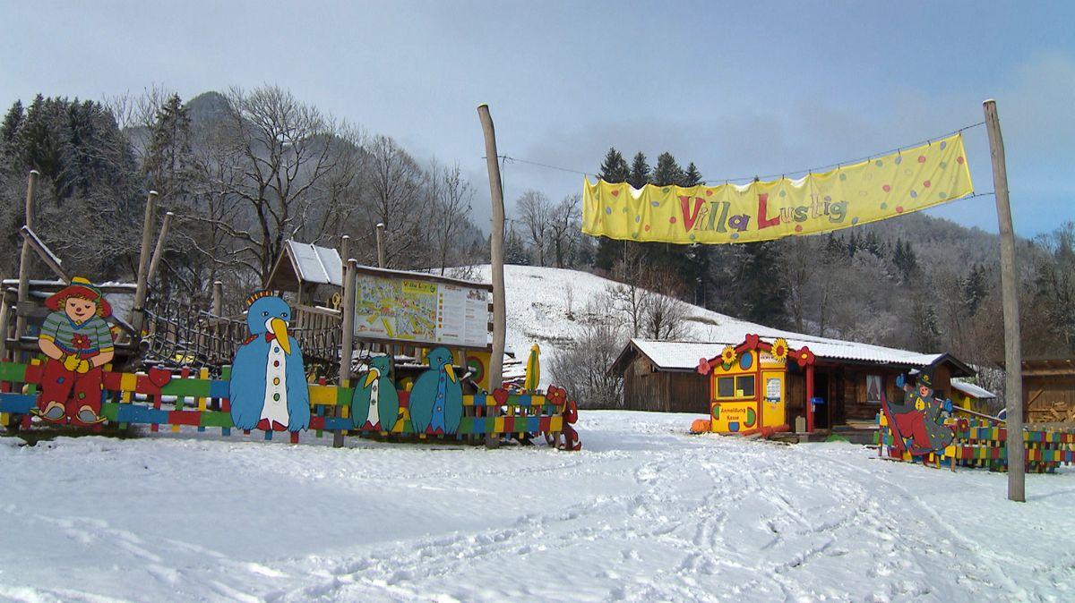 """Blick auf die """"Villa Lustig"""" der Skischule - mit Spuren von Skifahrern im Schnee davor."""