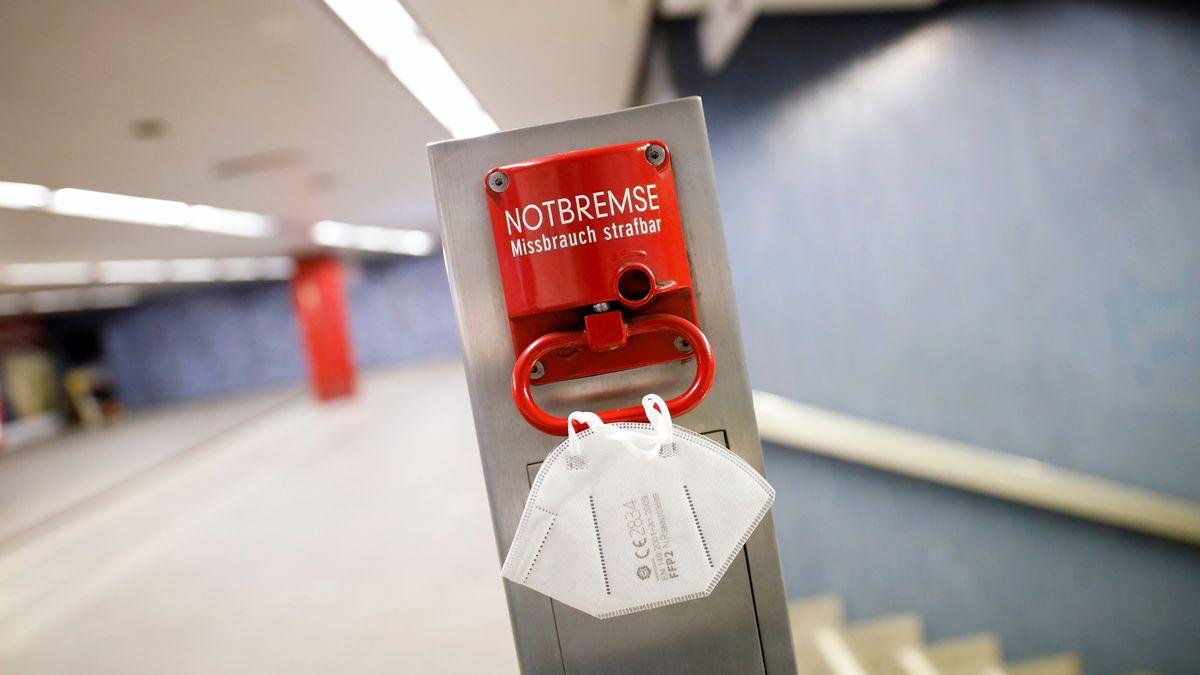 Eine FFP2-Maske hängt an einer roten Notbremse an einer Bahnhaltestelle (Symbolbild)