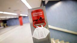 Eine FFP2-Maske hängt an einer roten Notbremse an einer Bahnhaltestelle (Symbolbild) | Bild:pa/dpa/Christoph Hardt