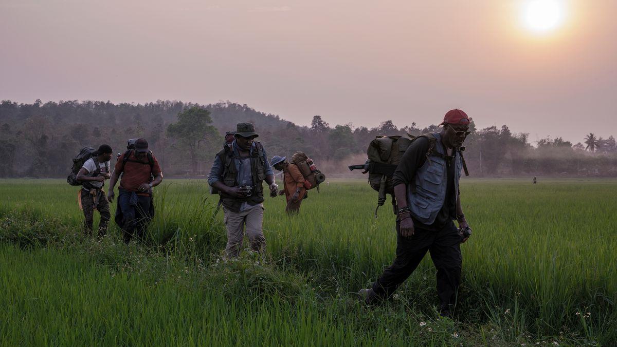 5 schwarze Soldaten gehen über ein Feld