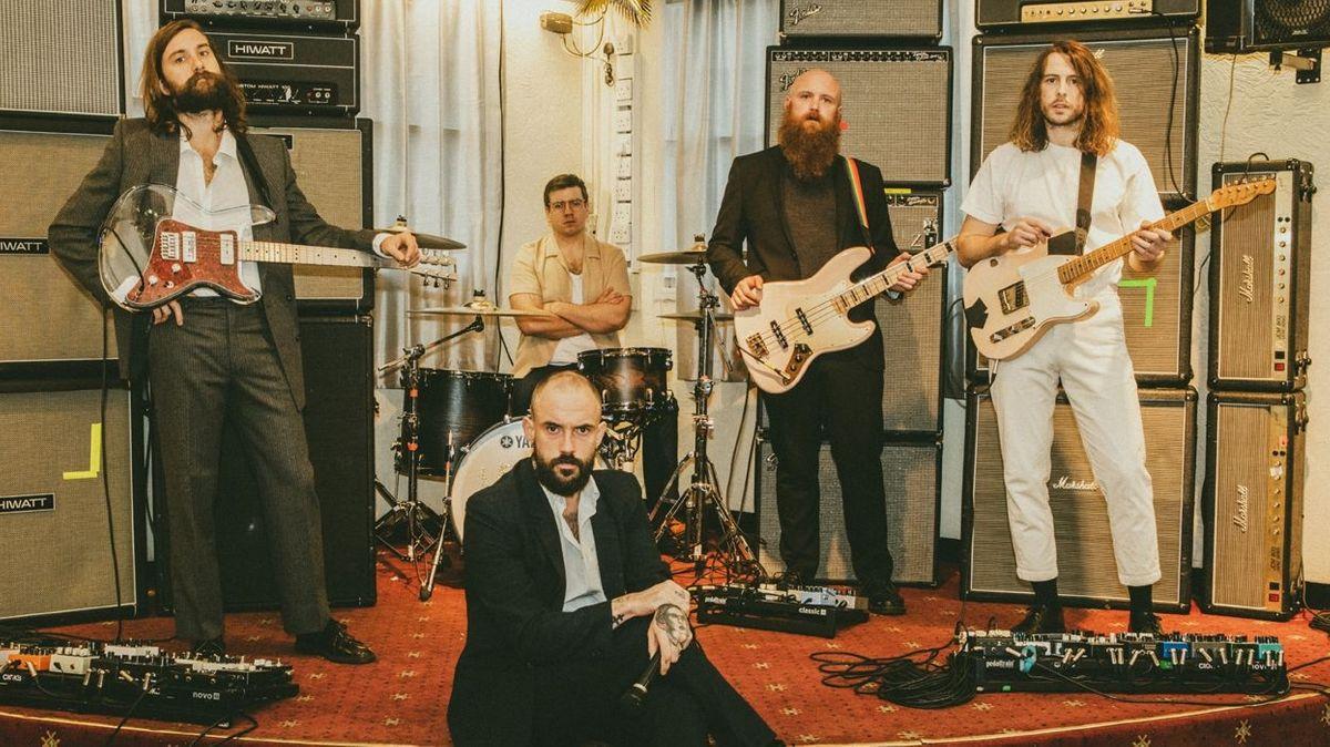 Das Post-Punk-Quintett Idles aus Bristol auf einer kleinen Bühne eines Clubs oder Hotels, Sänger Joe Talbot sitzt vorne am Bühnenrand mit Mikrofon in der Hand.