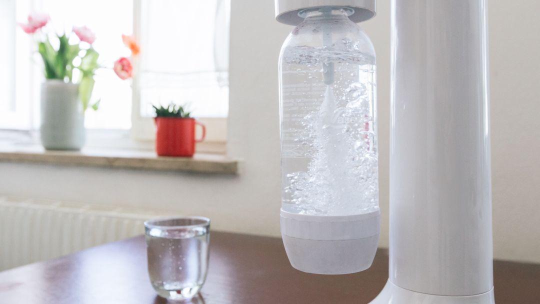 Ein Wassersprudler mit einem Glas Wasser im Hintergrund.