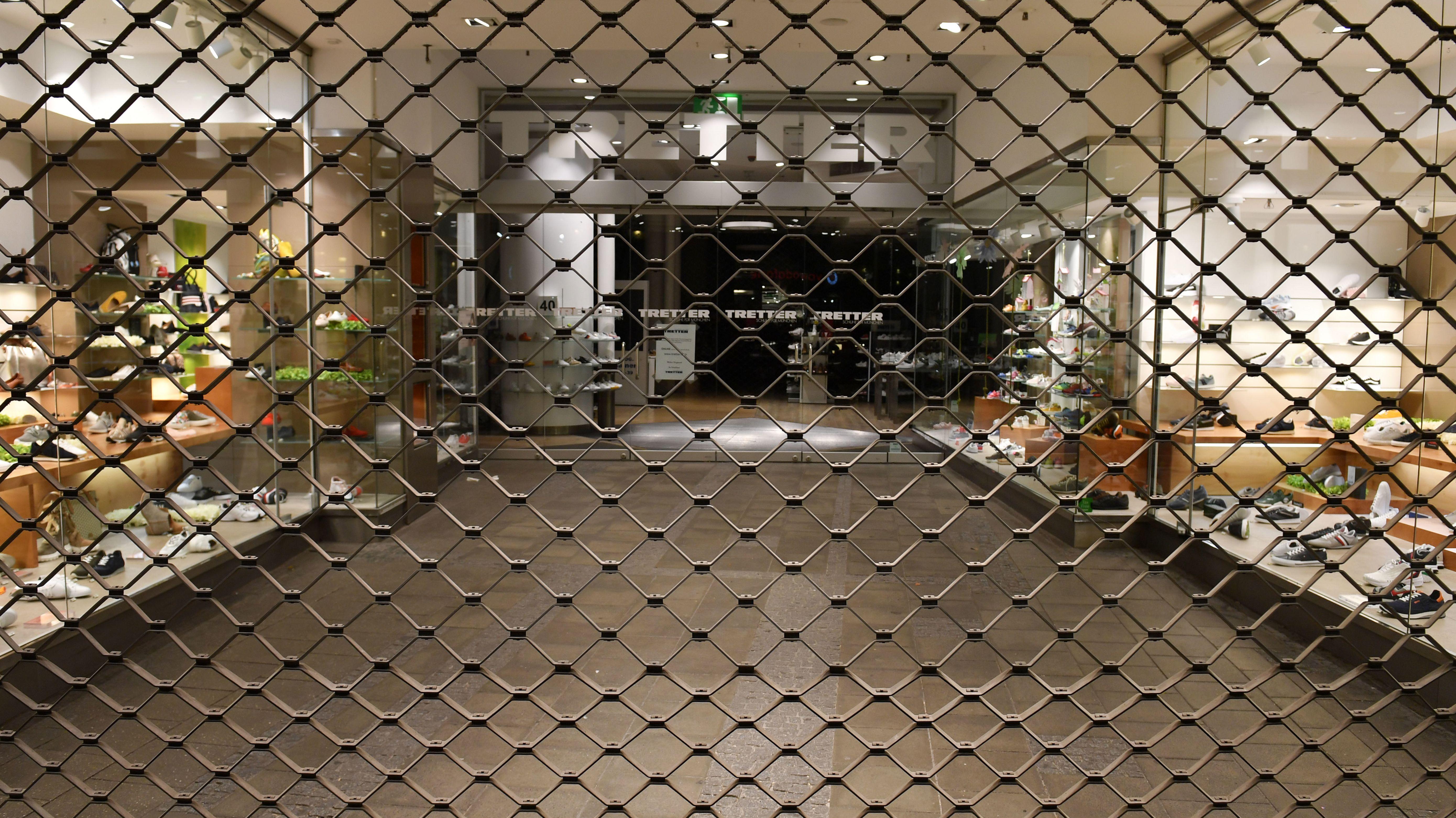 Vor einem Schuhgeschäft ist das Gitter heruntergelassen.