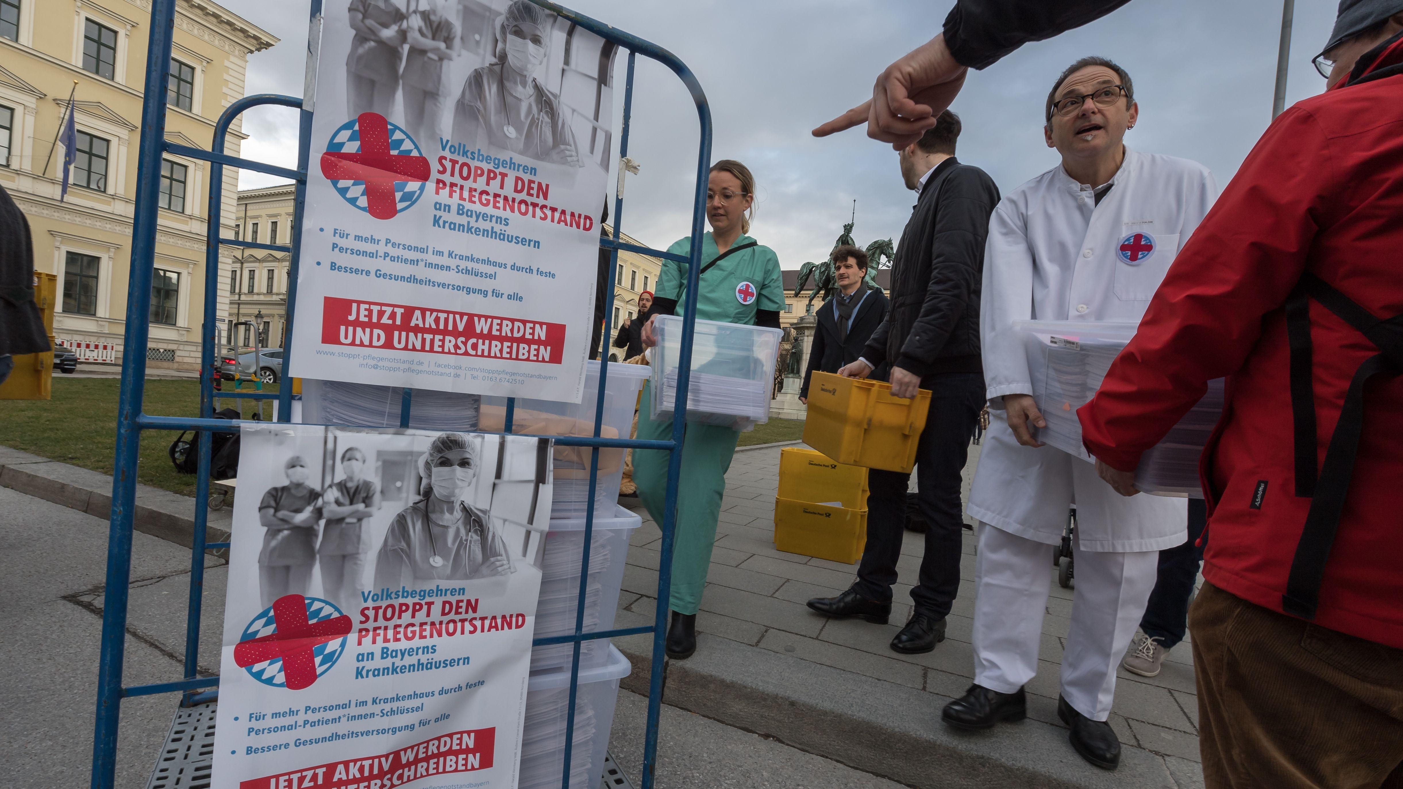 """Organisatoren des Volksbegehrens """"Stoppt den Pflegenotstand"""" überreichen vor dem bayerischen Innenministerium die Kisten mit den gesammelten Unterschriftenlisten."""