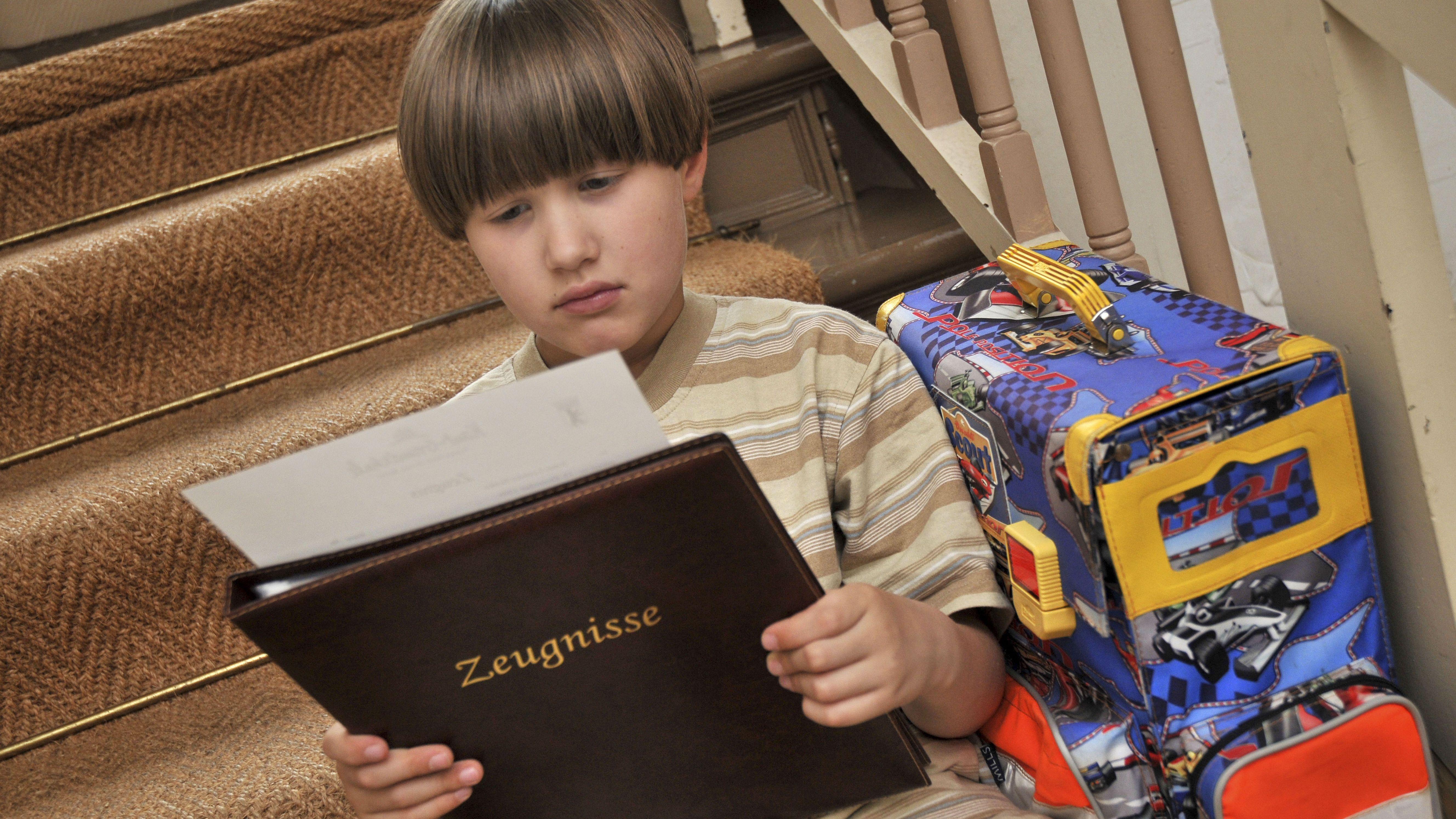 Junge sitzt auf der Treppe und liest Zeugnis