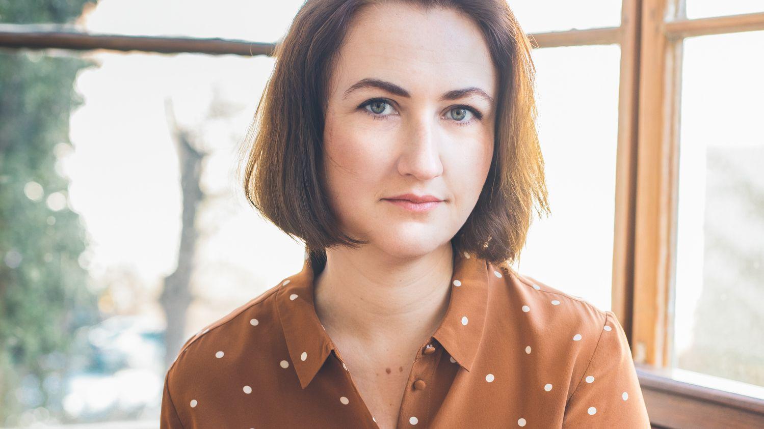 Die Autorin Emilia Smechowski blickt, vor einem Fenster sitzend, in die Kamera
