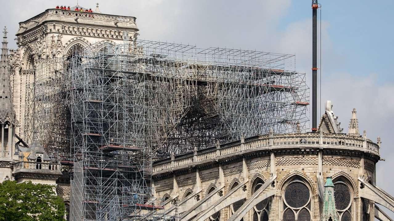 Feuerwehrmänner stehen auf dem Dach eines Turmes der Pariser Kathedrale Notre-Dame.