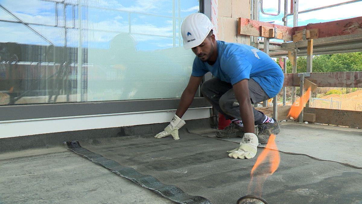 Samson Mahari, der einen weißen Helm und ein blaues T-Shirt trägt, dichtet auf einer Baustelle den Boden mit einer Bitumenplane ab.