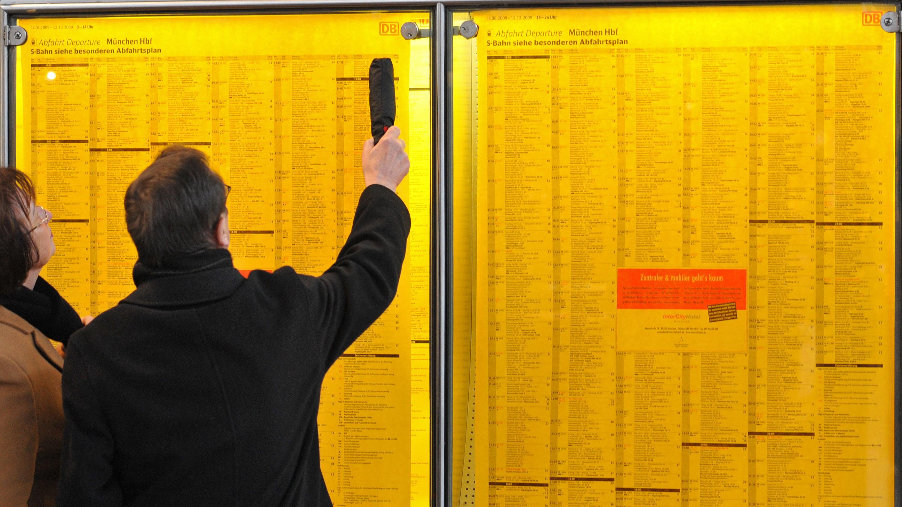 Ein Mann und eine Frau schauen am Münchner Haupbahnhof auf einen Fahrplan