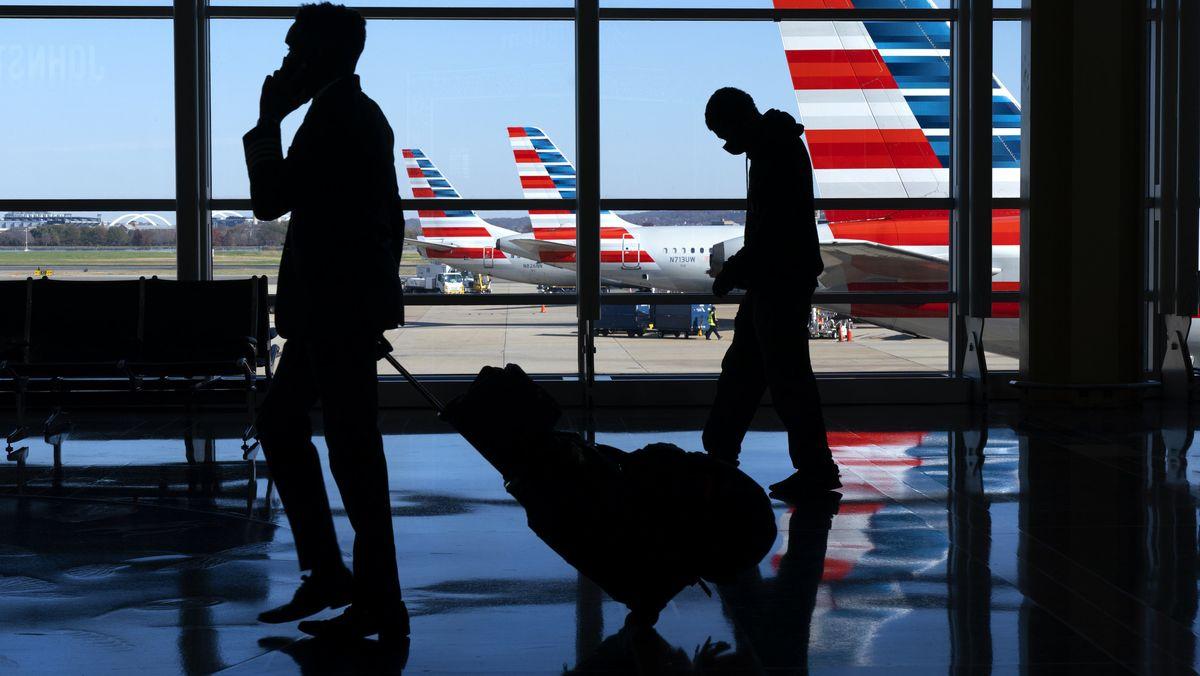 Reisende an einem Flughafen stehen vor einem großen Fenster mit Blick auf Flugzeuge