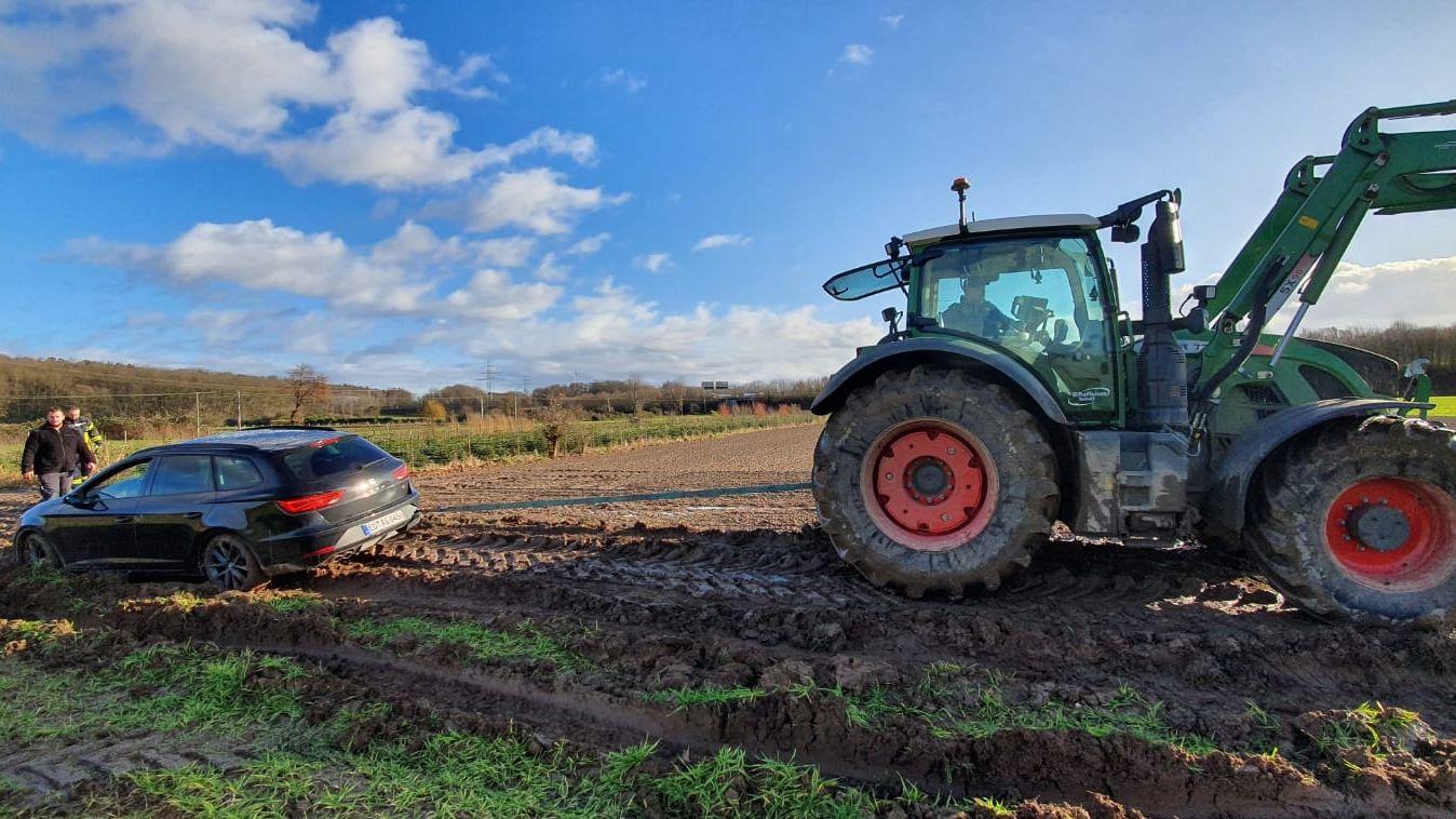 Ein Traktor zieht ein Auto aus einem schlammigen Acker.