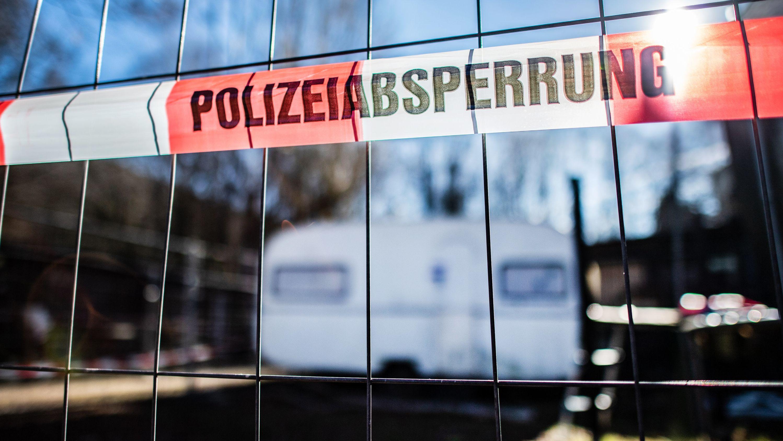 """Archivbild: Vor einem versiegelten Campingwagen hängt eine Banderole mit der Aufschrift: """"Polizeiabsperrung""""."""