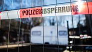 """Archivbild: Vor einem versiegelten Campingwagen hängt eine Banderole mit der Aufschrift: """"Polizeiabsperrung"""".   Bild:dpa / Guido Kirchner"""
