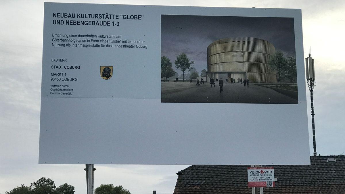 Ein Schild auf dem Baugelände zeigt einen Entwurf des Globe-Theaters: ein viergeschossiger, runter Bau aus hellem Holz.