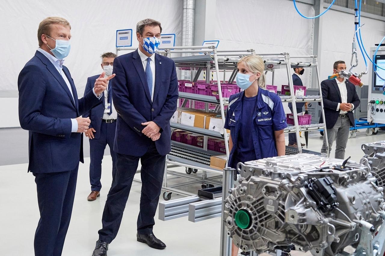 HANDOUT - 02.07.2020, Bayern, Dingolfing: Oliver Zipse (l-r), Vorstandsvorsitzender der BMW AG, und Markus Söder, Ministerpräsident von Bayern, nehmen an der offiziellen Eröffnung des Kompetenzzentrums E-Antriebsproduktion teil, neben ihnen steht eine Mitarbeiterin des Unternehmens. Foto: -/BMW/dpa - ACHTUNG: Nur zur redaktionellen Verwendung und nur mit vollständiger Nennung des vorstehenden Credits +++ dpa-Bildfunk +++
