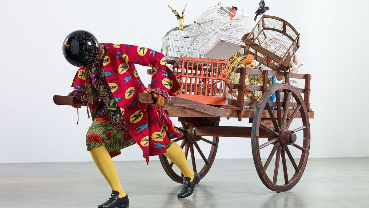 Vogelfänger-Statuette: Figur in historisierendem buntem Kostüm zieht einen Karren mit Vogelkäfigen