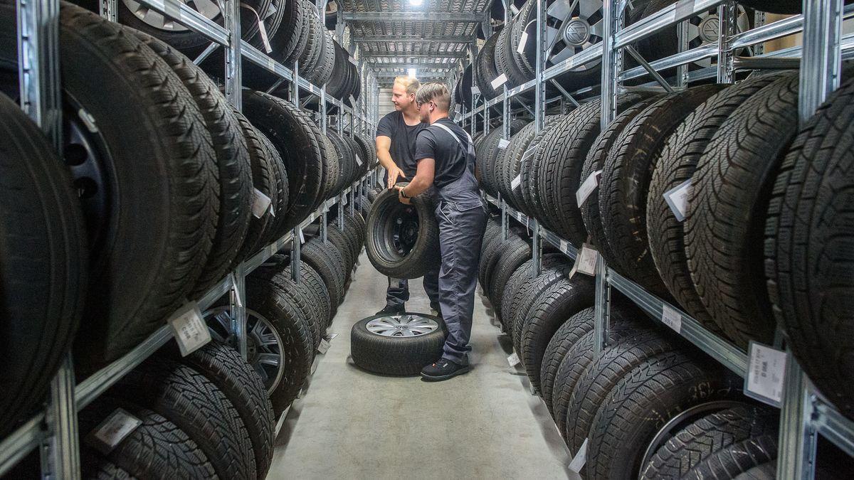 Zwei auszubildende Kfz-Mechatroniker heben in einem Lager Reifen aus dem Regal.