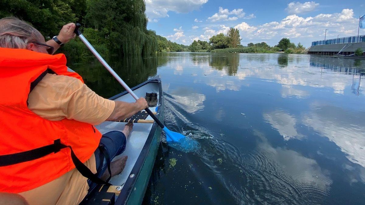 Ein Mann mit roter Schwimmweste paddelt in einem Kanu einem Wehr entgegen, im Hintergrund Bäume am Ufer und blauer Himmel mit Wolken.