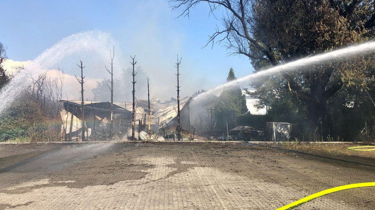 Die Feuerwehr löscht das niedergebrannte Büro- und Geschäftsgebäude